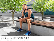 happy sportsman with bottle sitting on city bench. Стоковое фото, фотограф Syda Productions / Фотобанк Лори