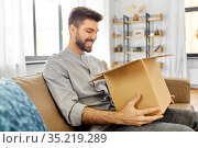 happy smiling man opening parcel box at home. Стоковое фото, фотограф Syda Productions / Фотобанк Лори