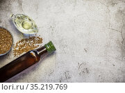 Linseed oil in a bottle, flax seeds, salad dressing in a gravy boat a source of omega-3 antioxidants vitamins and fatty acids on a table on a natural gray concrete background top view. Стоковое фото, фотограф Светлана Евграфова / Фотобанк Лори