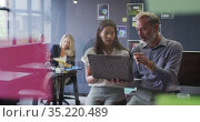 Two diverse business people using laptop talking in office and colleague working behind. Стоковое видео, агентство Wavebreak Media / Фотобанк Лори