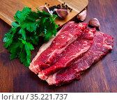 Raw marbled beef entrecotes with parsley and spices. Стоковое фото, фотограф Яков Филимонов / Фотобанк Лори