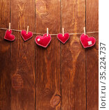 Concert for Valentine's Day. Red hearts made of felt pinned with clothespins to a string against background of boards. Стоковое фото, фотограф Сергей Молодиков / Фотобанк Лори