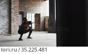 Shirtless african american man exercising with medicine ball in an empty urban building. Стоковое видео, агентство Wavebreak Media / Фотобанк Лори
