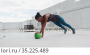 African american woman exercising doing push ups on medicine ball in an empty urban building. Стоковое видео, агентство Wavebreak Media / Фотобанк Лори