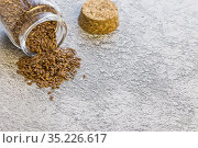 Herbal alternative medicine and cosmetology, flax seed in a glass jar piled on a table, a source of omega-3 proteins, magnesium iodine and antioxidants, a dietary supplement that reduces cholesterol. Стоковое фото, фотограф Светлана Евграфова / Фотобанк Лори