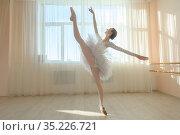 Beautiful ballerina in body and white tutu is training in a dance class. Young flexible dancer posing in pointe shoes. Стоковое фото, фотограф Михаил Решетников / Фотобанк Лори