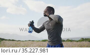 African american man pouring water on his face while exercising in countryside. Стоковое видео, агентство Wavebreak Media / Фотобанк Лори