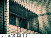Gloomy background with brick wall surface texture with scary window with metal rusty grating on the balcony in horror style with scary shadows and mystical light. Стоковое фото, фотограф Светлана Евграфова / Фотобанк Лори