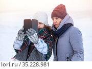 Two happy women friends sharing a smart phone after photo self shooting in cold winter lake shore. Стоковое фото, фотограф Кекяляйнен Андрей / Фотобанк Лори