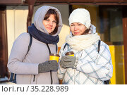 Girlfriend with paper cups with hot tea standing together dressed winter clothes with scarf and mittens, cold weather. Стоковое фото, фотограф Кекяляйнен Андрей / Фотобанк Лори