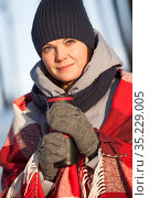 Attractive young Caucasian woman dressing woollen hat and mittens, wrapping in scarf holding thermo cup in hands, close up portrait. Стоковое фото, фотограф Кекяляйнен Андрей / Фотобанк Лори