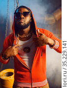 Rapper in red hoodie and sunglasses in studio. Стоковое фото, фотограф Tryapitsyn Sergiy / Фотобанк Лори