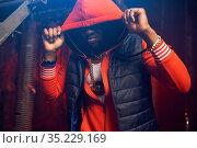 Rapper in red hoodie poses in grunge studio. Стоковое фото, фотограф Tryapitsyn Sergiy / Фотобанк Лори
