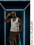 Rapper in gold jewelry poses in illuminated cube. Стоковое фото, фотограф Tryapitsyn Sergiy / Фотобанк Лори