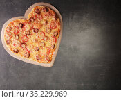 Delicious pizza in the form of a heart for valentine's day on dark table background. Стоковое фото, фотограф Сергей Молодиков / Фотобанк Лори