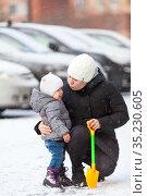 Mother quieten her crying toddler child on snowy street, hugging and kissing her son. Стоковое фото, фотограф Кекяляйнен Андрей / Фотобанк Лори