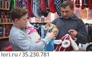 Father and son choose clothes for dogs in pet store. Стоковое видео, видеограф Яков Филимонов / Фотобанк Лори