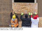 Detroit, Michigan USA - 18 January 2021 - Volunteers board up a burned... Редакционное фото, фотограф Jim West / age Fotostock / Фотобанк Лори
