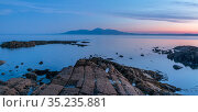 Rocky shore on St John's Point at sunset, mountains in distance across sea. Killough, County Down, Northern Ireland, UK. May 2020. Стоковое фото, фотограф Robert  Thompson / Nature Picture Library / Фотобанк Лори