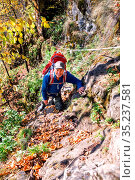 mature tourist walks along a narrow trail holding on to a rope over a cliff on an autumn sunny day. Стоковое фото, фотограф Акиньшин Владимир / Фотобанк Лори
