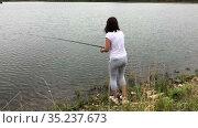 Attractive woman standing on lake shore with rod in hands, female fisher is on recreational fishing. Стоковое видео, видеограф Кекяляйнен Андрей / Фотобанк Лори