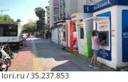 The largest Turkish Bankamatik network for withdraw cash. Group of ATM of different banks stand on the street for vacationers. Woman in mask uses atm. Alanya, Turkey. Редакционное видео, видеограф Кекяляйнен Андрей / Фотобанк Лори
