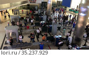 Luggage screening is in the Fraport TAV Antalya Airport. Crowds of passengers wearing masks pass the control points. Antalya, Turkey. Редакционное видео, видеограф Кекяляйнен Андрей / Фотобанк Лори