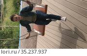 Vertical video of Caucasian woman swinging on the swings. Happy adult female enjoying on wooden urban playground. Стоковое видео, видеограф Кекяляйнен Андрей / Фотобанк Лори
