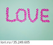 Word love made of small pink hearts on blue background. Стоковое фото, фотограф Мила Демидова / Фотобанк Лори