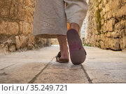 Detail shot of female legs wearing comfortable travel sandals walking on old medieval cobblestones street dring sightseeing city tour. Travel, tourism and adventure concept. Стоковое фото, фотограф Matej Kastelic / Фотобанк Лори