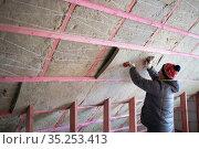 A man insulates an attic. Стоковое фото, фотограф Типляшина Евгения / Фотобанк Лори