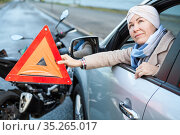 Woman a driver is at crash scene with car and motorcycle, triangle sign is in her hand. Стоковое фото, фотограф Кекяляйнен Андрей / Фотобанк Лори