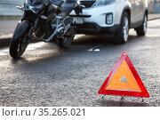 Rear-end collision on a road, suv car hits a motorcycle, emergency warning triangle is on asphalt roadside. Стоковое фото, фотограф Кекяляйнен Андрей / Фотобанк Лори
