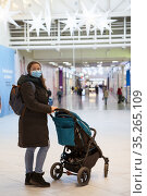 Full length portrait of an adult Caucasian woman in facial mask when walking with little child in a shopping mall. Стоковое фото, фотограф Кекяляйнен Андрей / Фотобанк Лори
