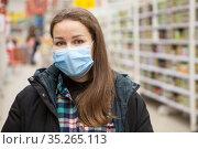 Wearing face mask in public places during the coronavirus pandemic, adult woman portrait against store shelves. Стоковое фото, фотограф Кекяляйнен Андрей / Фотобанк Лори