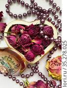 Засушенные бутоны роз в шкатулке в форме сердечка и бусы из сиреневого жемчуга. Редакционное фото, фотограф Мария Кылосова / Фотобанк Лори