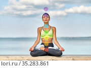 woman meditating in lotus pose with seven chakras. Стоковое фото, фотограф Syda Productions / Фотобанк Лори