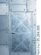 Background of silvery wall and door made of polyethylene foam sheets imitating metal with rivets. Стоковое фото, фотограф Serg Zastavkin / Фотобанк Лори