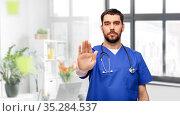 doctor or male nurse showing stop gesture. Стоковое фото, фотограф Syda Productions / Фотобанк Лори