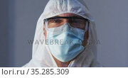 Portrait of caucasian male medical worker wearing protective clothing with mask and safety glasses. Стоковое видео, агентство Wavebreak Media / Фотобанк Лори