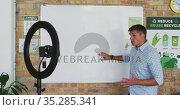 Caucasian male teacher standing at whiteboard giving an online lesson to camera. Стоковое видео, агентство Wavebreak Media / Фотобанк Лори