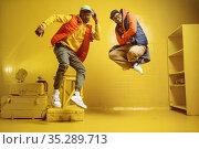 Two stylish rappers in studio, yellow background. Стоковое фото, фотограф Tryapitsyn Sergiy / Фотобанк Лори