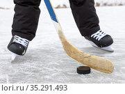Close-up view at black puck and hockey skates on lake ice, teenage male legs, front view. Стоковое фото, фотограф Кекяляйнен Андрей / Фотобанк Лори