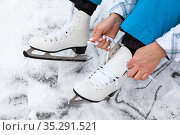 Woman sitting on lake ice, wearing figure skates and ties shoelaces with hands, close up-view. Стоковое фото, фотограф Кекяляйнен Андрей / Фотобанк Лори