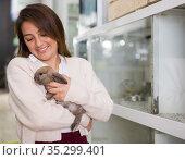 Happy woman holding rabbit in pet shop. Стоковое фото, фотограф Яков Филимонов / Фотобанк Лори
