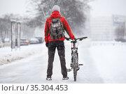 Rear view of an adult man with bicycle standing on snowy bike lane on an urban streets, winter season with snowfall. Red jacket and grey backpack. Стоковое фото, фотограф Кекяляйнен Андрей / Фотобанк Лори