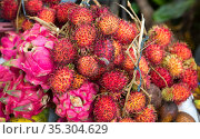 Красные фрукты драгон фрут (dragon fruit) и рамбутана лежат на прилавке. Индонезия. (2018 год). Стоковое фото, фотограф Галина Савина / Фотобанк Лори