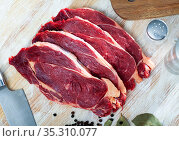 uncooked beef marbled steak served with pepper on the table. Стоковое фото, фотограф Яков Филимонов / Фотобанк Лори