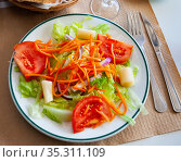 Mediterranean salad with tomato, lettuce and carrot on white plate on wooden table. Стоковое фото, фотограф Яков Филимонов / Фотобанк Лори