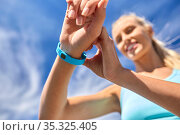 smiling young woman with fitness tracker outdoors. Стоковое фото, фотограф Syda Productions / Фотобанк Лори